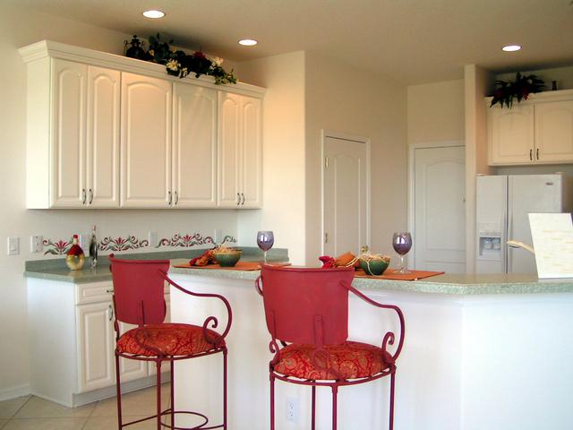 bílá kuchyně s červenými židlemi